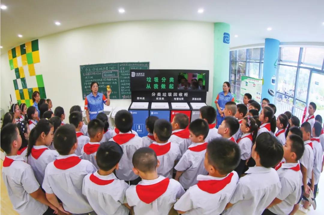 小学生认真聆听环卫工人讲解垃圾分类的重要意义
